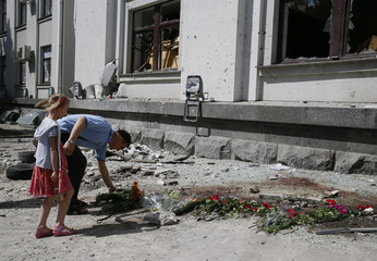 A man places flowers near the site of an explosion in a regional administration building in Luhansk
