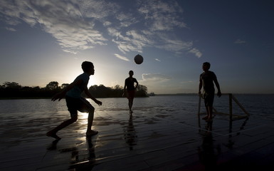 Boys play soccer on a driftwood soccer court, on the banks of the Rio Negro or Black River in Catalao community near Manaus