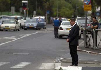 Israelis stand still on a street in Jerusalem as a two-minute siren marking Holocaust Remembrance Day is sounded
