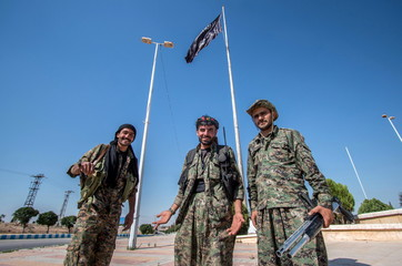 YPG fighters stand near an Islamic State flag in Tel Abyad town