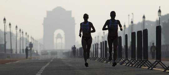 England's Decker and Rush run past India Gate while competing in the women's marathon final during the Commonwealth Games in New Delhi