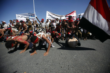 """Anti-government protesters pray on the road to Sanaa at the end of a five-day """"March of Dignity"""" from the Red Sea city of Houdieda"""