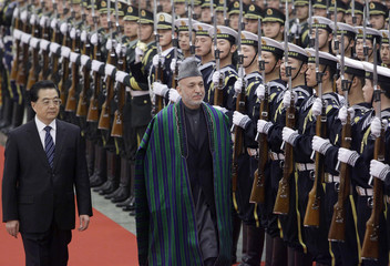Afghanistan's President Karzai and China's President Hu inspect honour guards inside the Great Hall of the People in Beijing