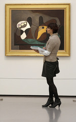 A woman stands in front of the painting 'Fruit Bowl and Guitar' by late Spanish artist Picasso during a media preview at the Kunsthaus Zurich in Zurich