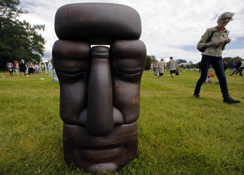 """A visitor walks past a ceramic figure """"Nirvana"""" during """"Glass and Ceramics in the Landscape"""" in central park in St. Petersburg"""