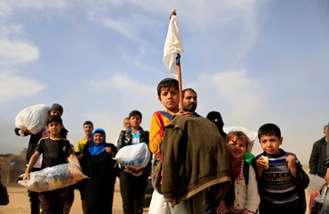 A displaced Iraqi boy holds up a white flag while fleeing Samah neighborhood during a fight between Islamic State militants and the Iraqi Counter Terrorism Service in Mosul, Iraq