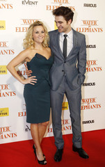 "Reese Witherspoon and Robert Pattinson pose on the red carpet at the Australian premiere of the film ""Water for Elephants"" at the State Theatre in Sydney"