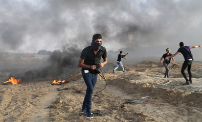 Masked Palestinian protester takes a position during clashes with Israeli troops near the border between Israel and Central Gaza Strip