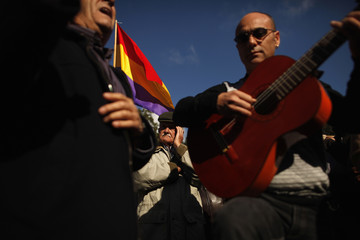 A man listens as flamenco musicians perform after the burial of human skeletal remains inside a pantheon at a cemetery in the neighborhood of La Sauceda