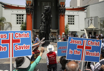 A parade of evangelical Christians chant religious slogans near a statue of movie monster Godzilla in front of the TCL Chinese Theatre IMAX forecourt on Hollywood Boulevard in California