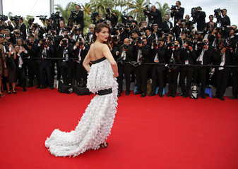 Actress and former fashion model Laetitia Casta poses on the red carpet as she arrives for the opening ceremony of the 67th Cannes Film Festival in Cannes