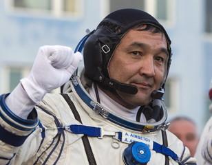 Cosmonaut Aidyn Aimbetov of Kazakhstan gestures donning space suits at the Baikonur cosmodrome, Kazakhstan