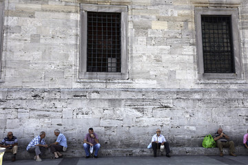 People rest in front of the Ottoman-era New Mosque in Istanbul
