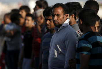 Migrants line up at the port of Kos following a rescue operation off the Greek island of Kos