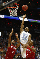 North Carolina Tar Heels guard Watts jumps for a rebound against North Carolina State Wolfpack guards Brown and Johnson during their college basketball game in Atlanta