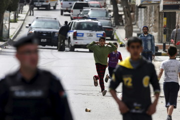 Children gather as officers of the Jordanian public security department stand guard in the northern city of Irbid