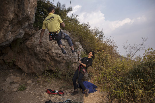 Rock climber Nazia Parveen jokes with her trainer Imran Junaidi during their practice in Islamabad