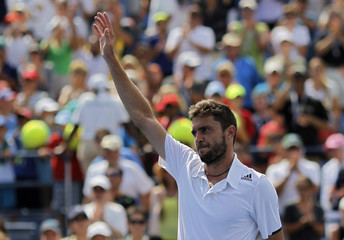 Gilles Simon of France waves after his win over David Ferrer of Spain during their match at the 2014 U.S. Open tennis tournament in New York
