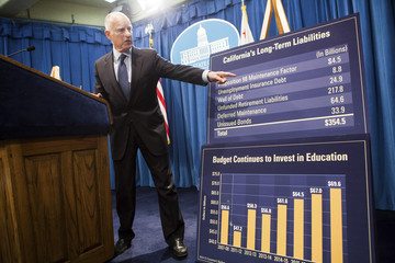 California Governor Brown gestures at graph detailing the state's long-term liabilities while unveiling his proposed 2014-15 state budget in Sacramento