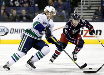 Vancouver Canucks' Booth takes puck by Columbus Blue Jackets' Letestu during NHL hockey game in Columbus