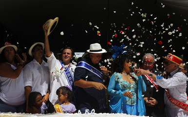 Mayor Eduardo Paes holds up his hat as he stands with a 450-metre long cake that was prepared as part of celebrations to mark the 450th anniversary of the city of Rio de Janeiro