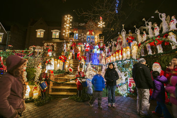 Passerbys stop to have their photograph taken as they look at a house in the Dyker Heights neighborhood of Brooklyn lit up with Christmas decorations in New York