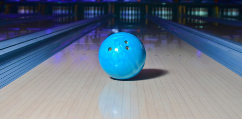 Blue bowling ball on the track. Active leisure. Sport game.