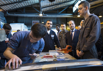 French President Francois Hollande speaks with automobile mechanic students and teaching staff during his visit to the Institute of Artisanal Trades in Villiers-le-Bel