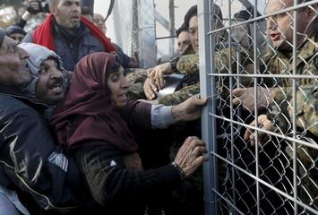 Syrian refugees struggle to enter Macedonia through a narrow border crossing as Macedonian policemen try to shut a metal gate near to the Greek village of Idomeni