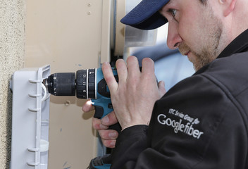 Google Fiber technician Ohngren, installs a fiber optic box at a residential home in Provo