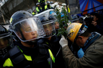 A man holding flowers leans on a shield of a riot policeman as they march toward the Presidential Blue House during a protest calling for South Korean President Park Geun-hye to step down in central Seoul