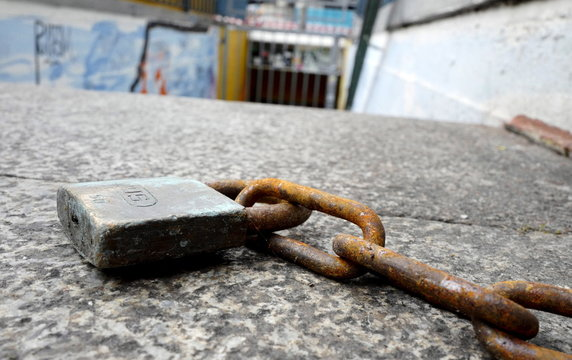 """A lock and chain are seen next to the closed gate in front of music club """"White Rabbit"""" in Freiburg"""