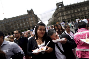 A couple holds a cake as they pose for a photo after a mass wedding ceremony in which 2,016 couples participated, at Zocalo square in Mexico City
