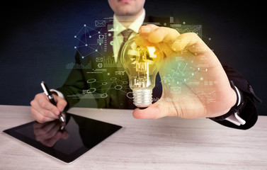 businessman holding glowing glass light bulb