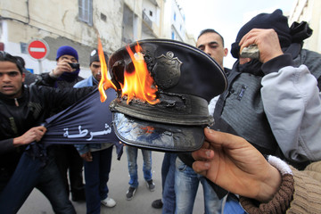 Rioters burn a policeman's hat during clashes with the police in downtown of the capital Tunis