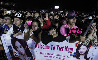 Vietnamese fans stand next to a banner with images of South Korean girl band Girls' Generation at a Kpop festival in Hanoi