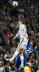 Real Madrid's Toni Kroos is challenged by Schalke 04's Huntelaar during their round of 16 second leg soccer match in Madrid