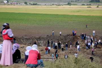 People gather at the site of last night's explosion near the Kurdish-dominated southeastern city of Diyarbakir