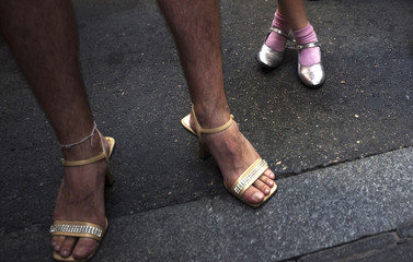 A girl stands next to a contestant before the annual race on high heels during Gay Pride celebrations in the quarter of Chueca in Madrid