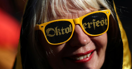 """A woman wears sunglasses that read """"Oktoberfest"""" at Argentina's Oktoberfest in Villa General Belgrano"""