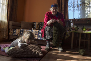 Circassian villager Ashirkhan Chachukh and her great-grand daughter sit in the living room of their house in the village of Tkhagapsh in the Lazerevskoye district of Sochi
