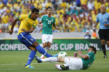 Brazil's Paulinho fights for the ball with Mexico's Moreno during their Confederations Cup Group A soccer match at the Estadio Castelao in Fortaleza