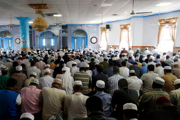 Community members pray inside of a mosque before the funeral service of Akonjee, and Uddin in the Queens borough of New York City