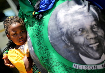 A girl looks on in front of a banner showing late South African president Nelson Mandela during the African National Congress party's 104th anniversary celebrations in Rustenburg