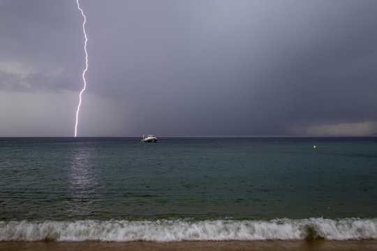 Lightning strikes as a small boat is seen at the beach in the northern Greek village of Toroni