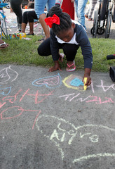 Tori Clemens draws with chalk on the sidewalk before a neighborhood celebration to celebrate the life of the late Muhammad Ali, former world heavyweight boxing champion at Ali's childhood home in Louisville