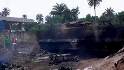 Still image taken from video shows people standing near a burnt gasoline tanker that crashed on the east-west road in Nigeria's oil-producing Niger Delta