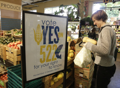 A customer picks up produce near a sign supporting a ballot initiative in Washington state that would require labelling of foods containing genetically modified crops at the Central Co-op in Seattle, Washington