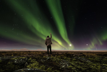 landscape of amazing beautiful  natural phenomenon Aurora Borealis, with a man raising arm , traveling in Iceland