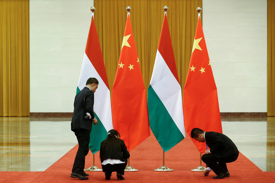 Officials arrange Chinese and Hungarian flags before talks between officials of the two countries at the Great Hall of the People in Beijing